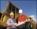Dave Torkelson, vice president of equipment at TARCO, reviews cost records with equipment operator John Smith