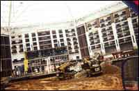"""Skid-steers build walls to stabilize the banks of a man-made """"river"""" running through the atrium of a new commercial structure."""
